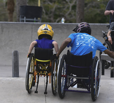 A manual wheelchair user is shown holding the wheel of a younger, manual wheelchair user positioned to his left. They are both wearing motorcycle helmets, looking over the quarter pipe in front of them.