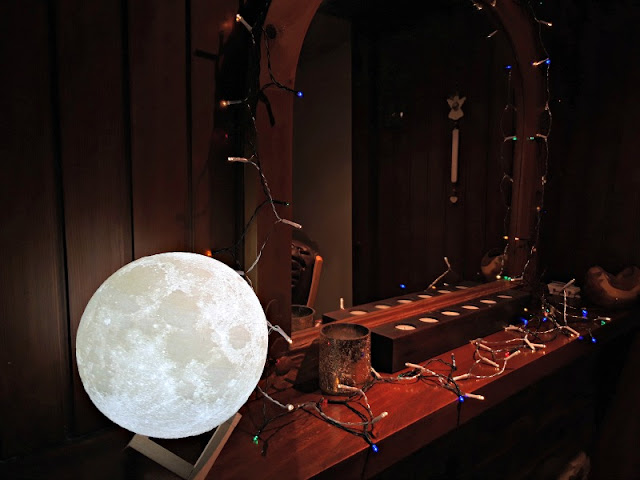 A photo with a glowing moon replica lamp in the foreground, and fairy lights and unlit candles in the background with a mirror in a wooden frame