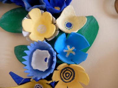 close up of flowers on blue and yellow egg carton wreath