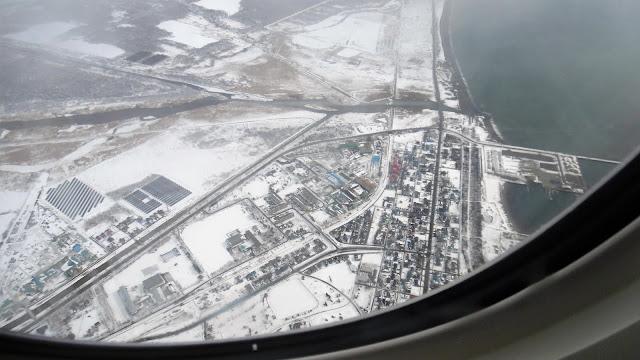 飛行機の窓から見た雪で覆われた北海道の大地