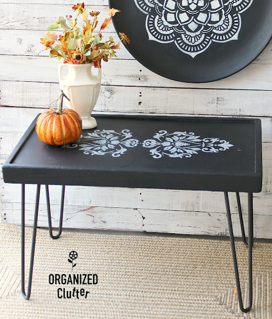 Photo of a coffee table upcycled with black paint and damask stencils.
