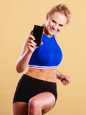 A photo of a woman looking at her phone as she works out.