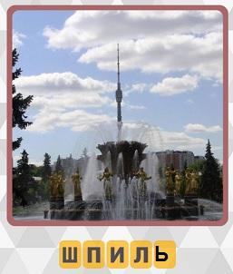 на выставке в Москве стоит башня со шпилем на заднем плане, впереди фонтан