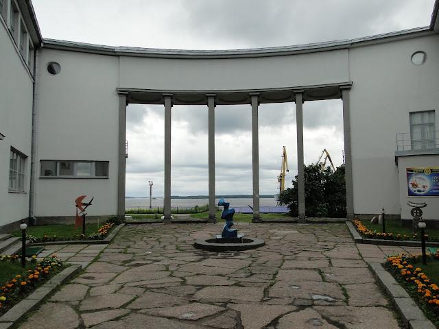 Taidekoulu ja -museorakennuksen sisäpihan pylväiden välistä on näkymä merelle. Värivalokuva.