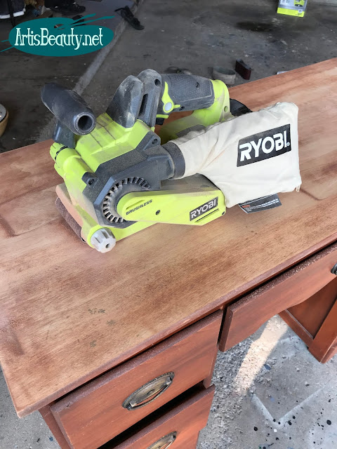 ryobi cordless belt sander used to remove old finish and gouges from old desk top in makeover