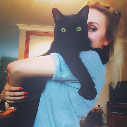 woman in blue t-shirt holding black cat over shoulder