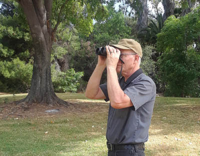 Photo of Greg Gillson watching birds with binoculars