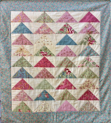 A lap quilt of triangles made from charm squares