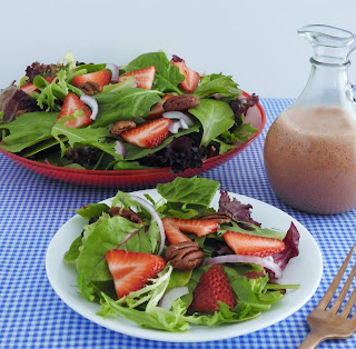 strawberry salad on blue and white tablecloth with bottle of dressing