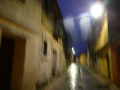 Calle solitaria en noche lluviosa. Sombras y luces reflejándose en el suelo mojado.
