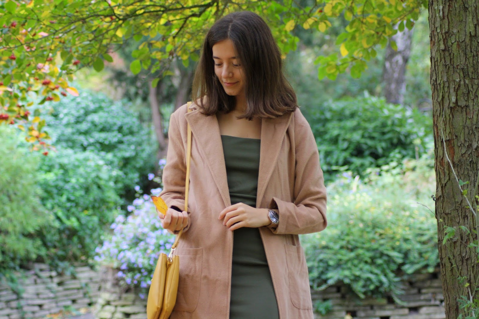 brunette standing amongst autumn leaves, wearing brown jacket and khaki dress