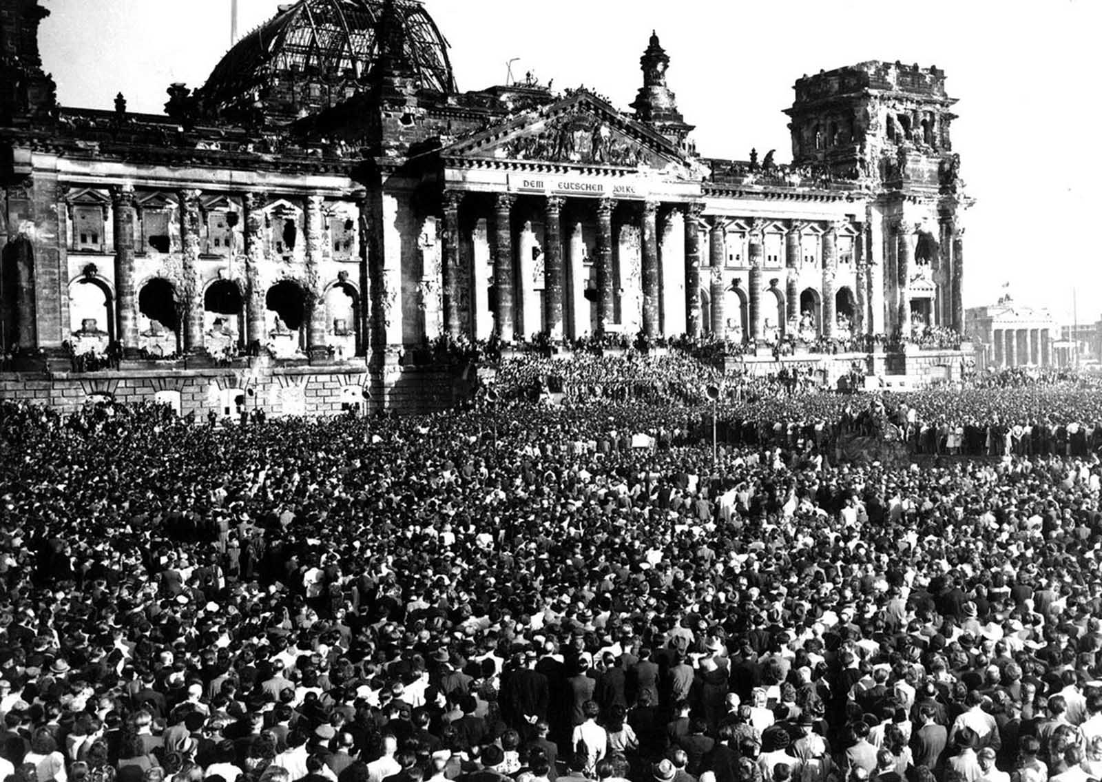 The scene in Berlin's Republic Square, before the ruined Reichstag Building, on September 9, 1948, as Anti-Communists, estimated at a quarter of a million, scream their opposition to Communism. At the time, the Soviet Union was enforcing the Berlin Blockade, blocking Allied access to the parts of Berlin under Allied control. In response, Allies began the Berlin Airlift until the Soviets lifted the blockade in 1949, and East Germany and West Germany were established. When the meeting pictured here broke up, a series of incidents between Anti-Red Germans and Soviet troops brought tension to a fever pitch as shootings took place, resulting in the deaths of two Germans.
