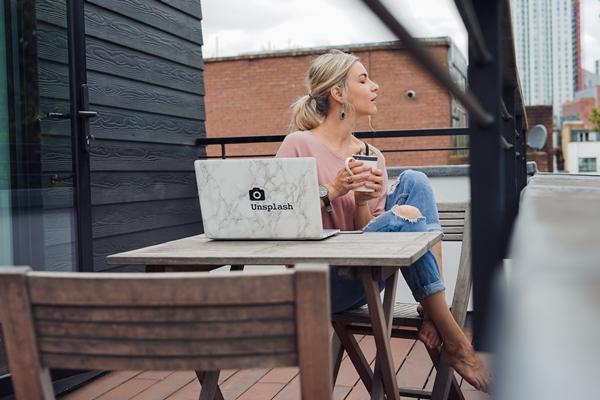 Mulher sentada à mesa de um café em frente ao seu notebook segurando uma xícara