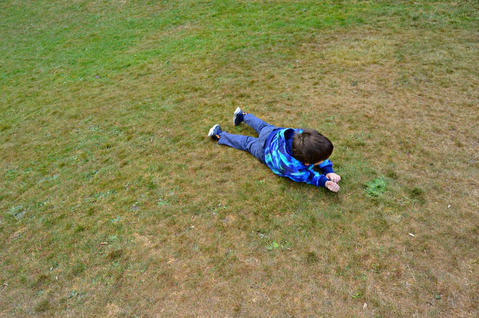 boy rolling down a hill