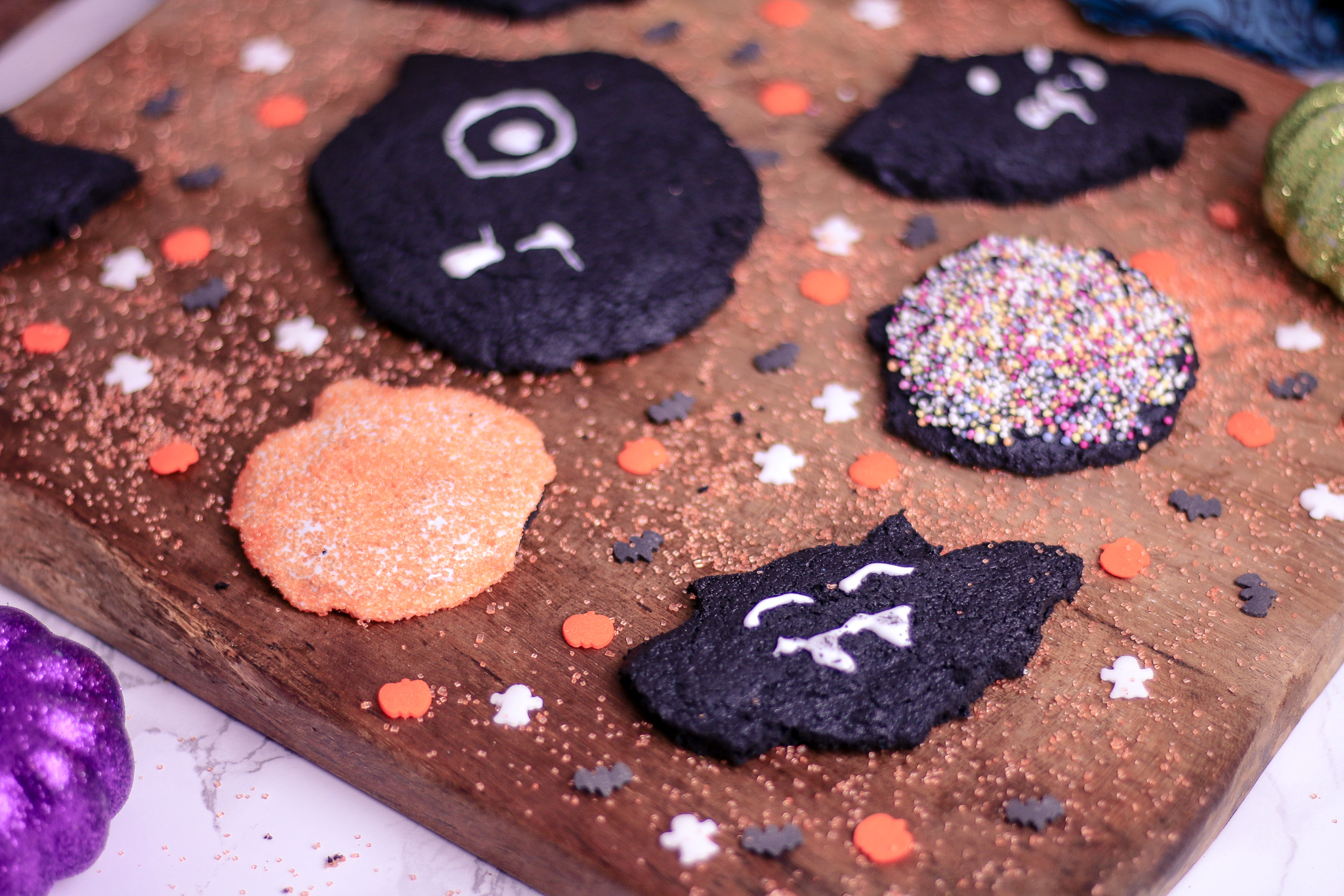 Side view photo of some bat and pumpkin biscuits on a wooden chopping board