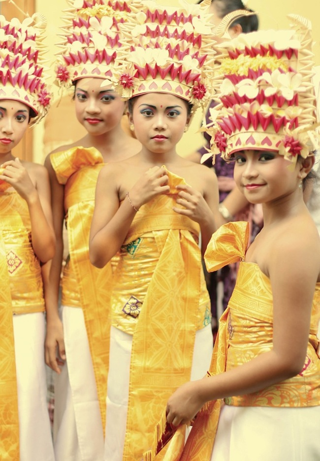 balinese religious ceremony with girls in traditional costumes