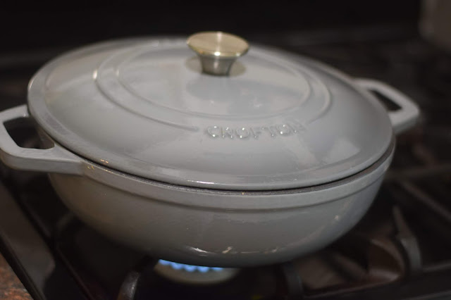 The dutch oven on the strove with the lid on it.