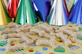 Homemade bone shaped dog treats and party hats at dog birthday party.