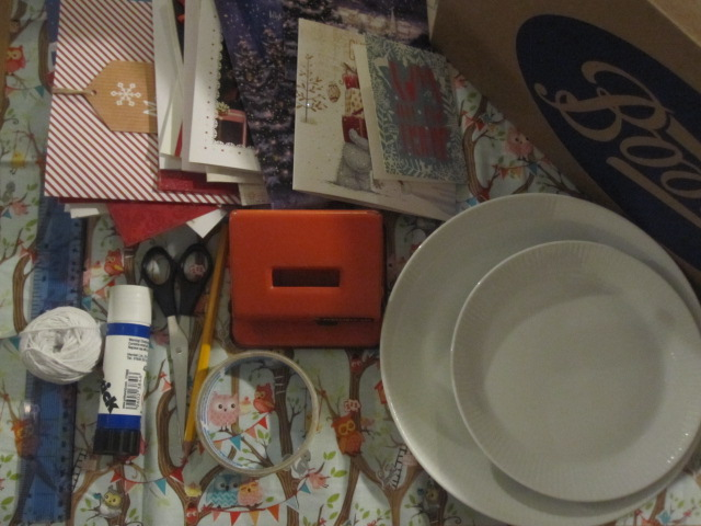 A pile of Christmas cards with a ruler, scissors, string, pencil, glue, tape and two plates of different sizes