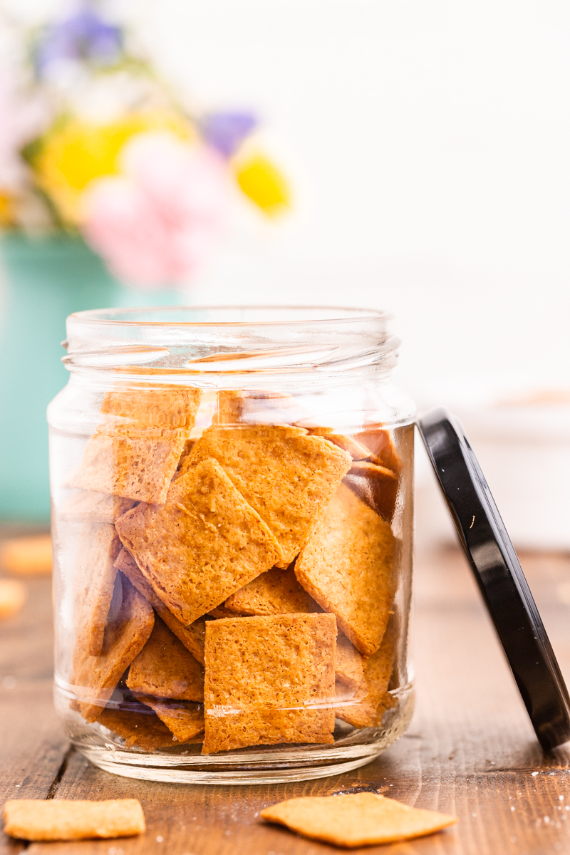 Photo of Keto Smoked Cheddar Crackers (Cheez-Its)  in a glass jar on a wooden table with the sun shining on it.