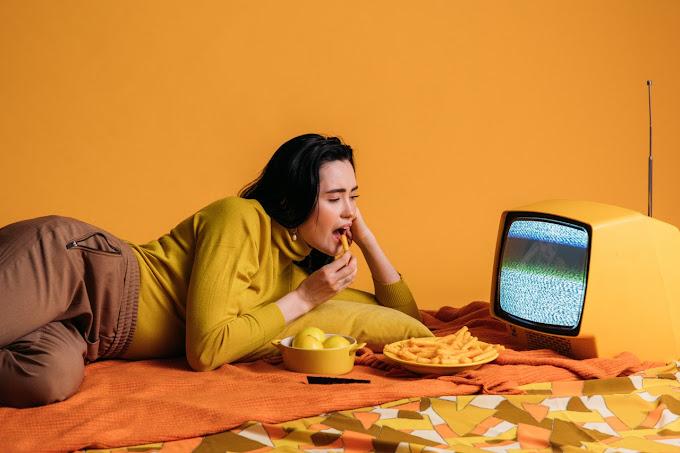 Mulher deitada de lado, comendo batata frita e olhando para uma TV amarela antiga que está com estática na tela. Toda a foto está em tons de amarelo. Ao lado do prato de batata frita, tem uma panela com frutas amarelas.
