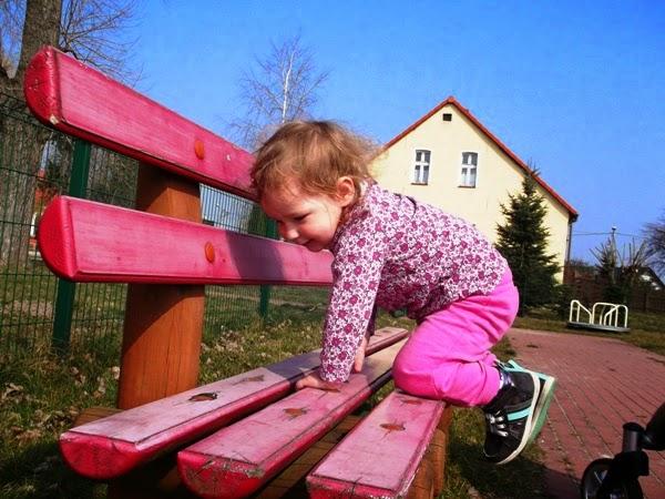 dziecko na placu zabaw, na ławce, uśmiechnięta dziewczynka