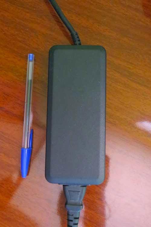 Fotografia da fonte do modem. Ela é maior em altura que uma caneta BIC, que está ao lado. Lembra muito a fonte de um notebook.