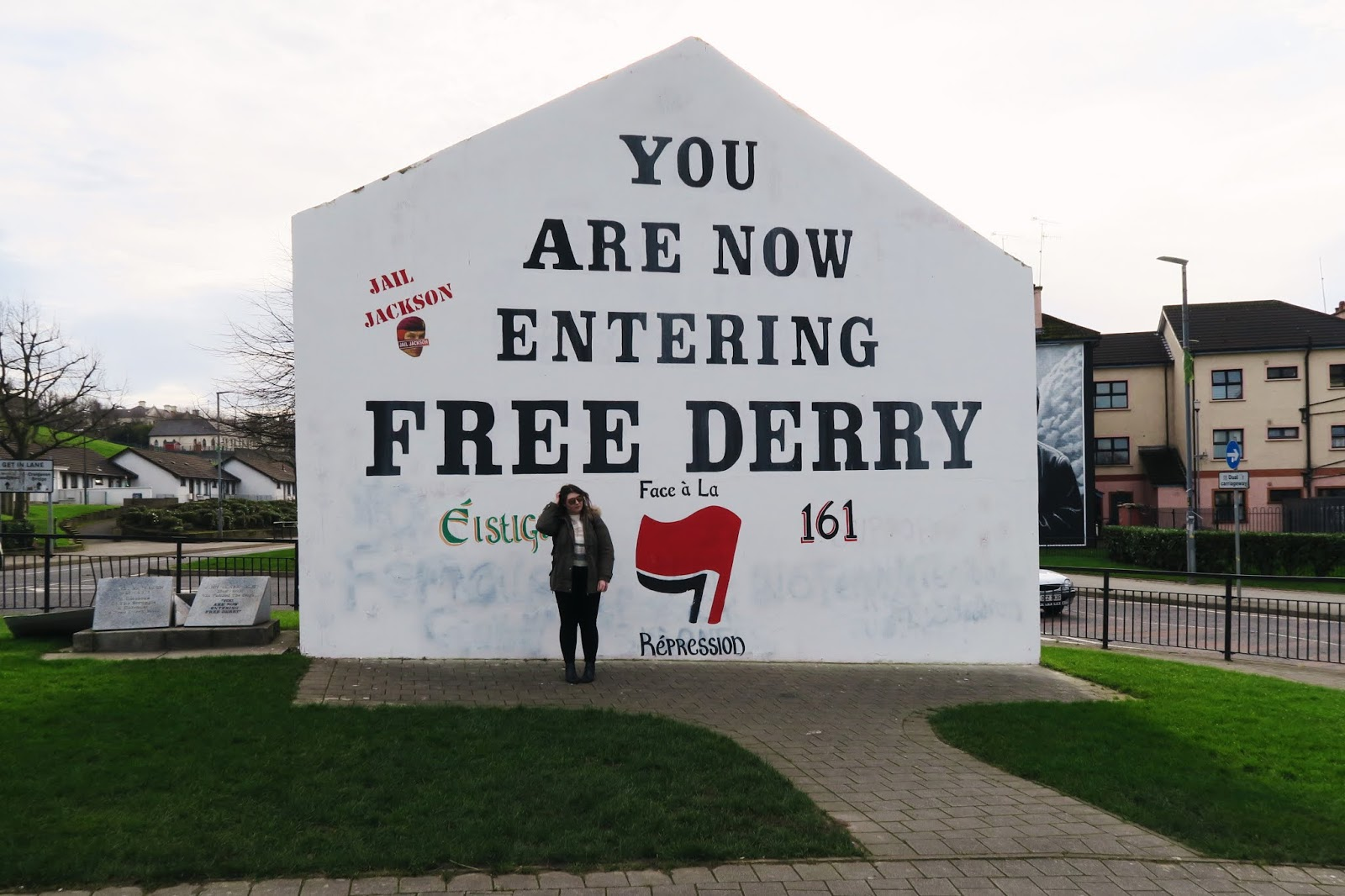 Myself standing in front of Free Derry Corner. I had to ask a strange to take this photograph as I was travelling solo