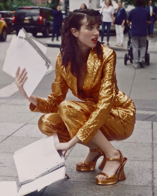 Woman on street in gold suit