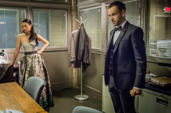 Jonny Lee Miller and Lucy Liu as Sherlock Holmes in a bow tie vest and Joan Watson in CBS Elementary Season 2 Episode 13 All in the Family