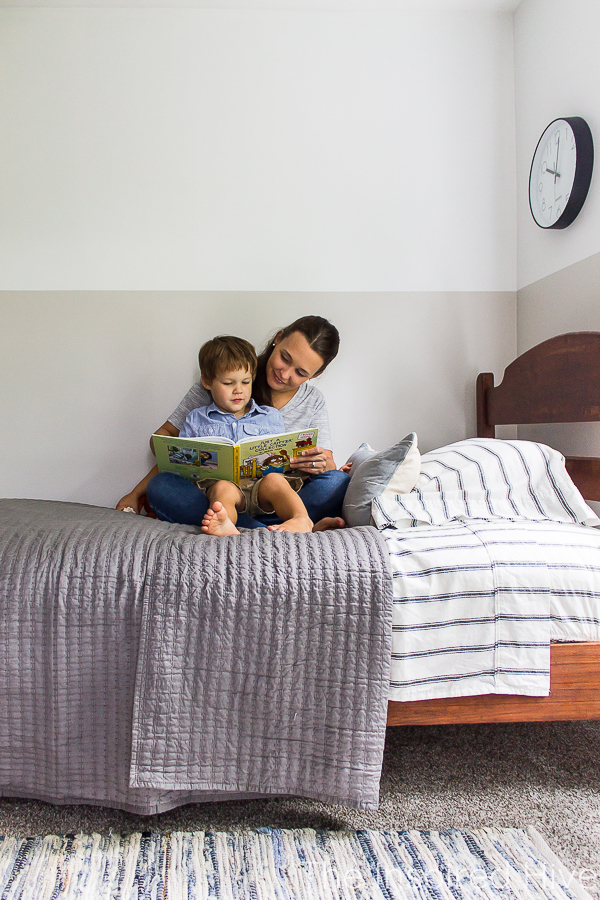 Reading books to toddler at bedtime. Boy's bedroom with antique bed, grey quilt, denim rug.