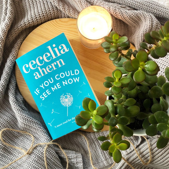Blue cover of 'If you Could See Me Now' by Cecelia Ahern next to a white candle and green money plant