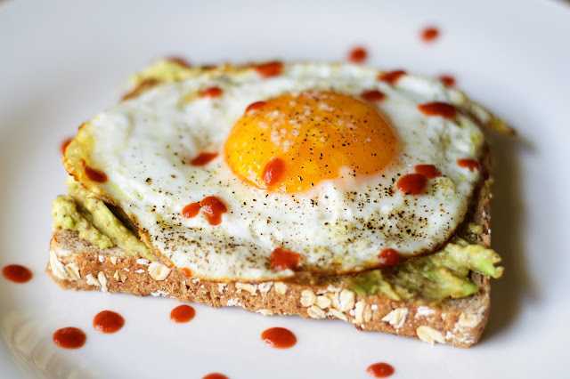 The finished Avocado Toast with Egg and Sriracha on a white plate!