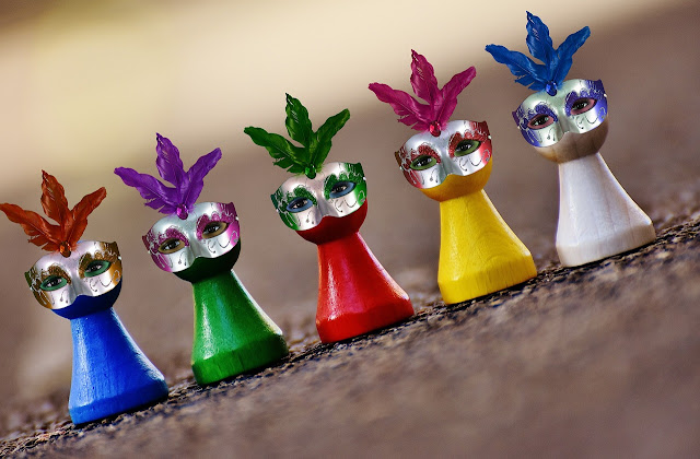 Five board game player pieces wearing Carnival masks.