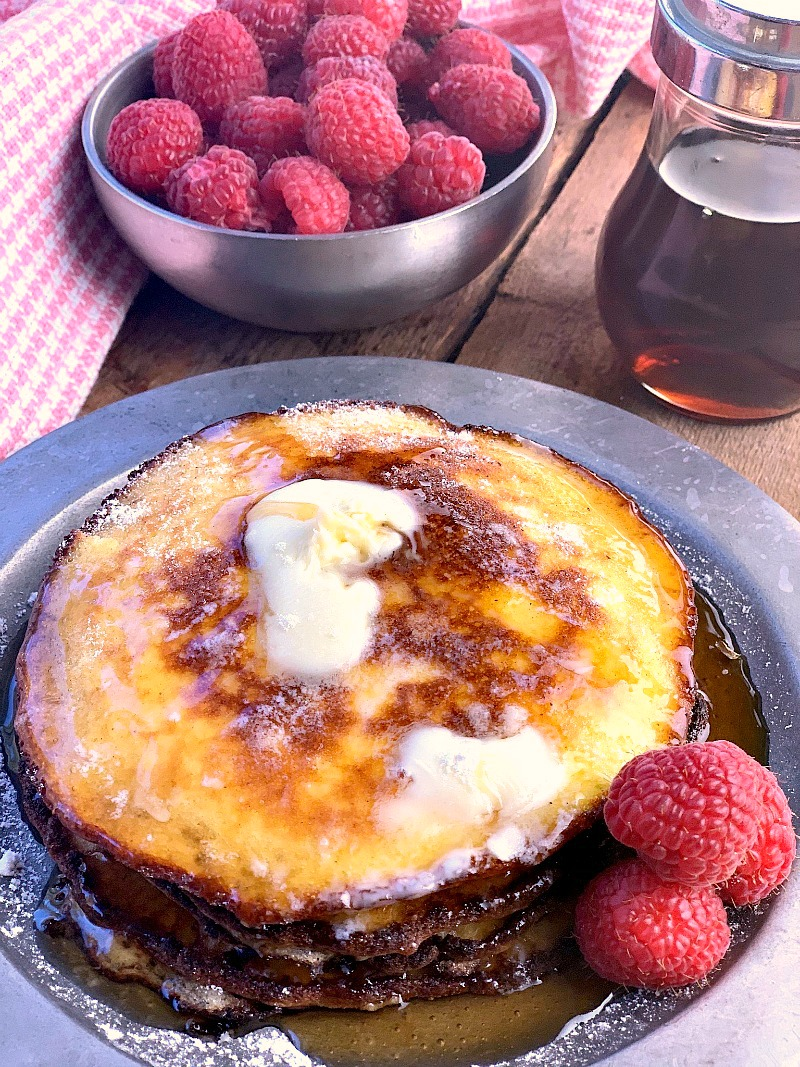 Photo of Cream Cheese Pancakes on a metal plate with butter and syrup on them and berries in a bowl on the side.