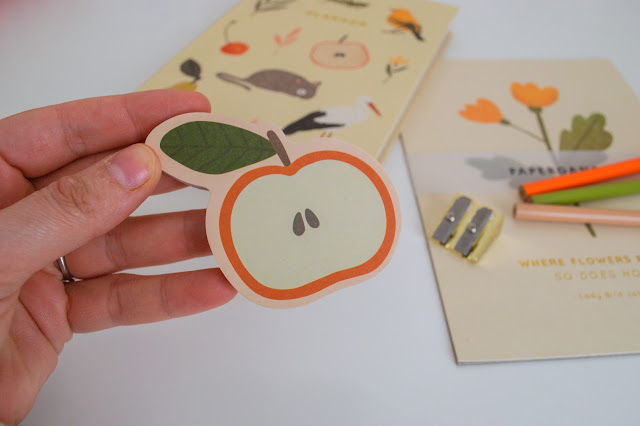 Hand holding die cut sticky notes in the shape of an apple