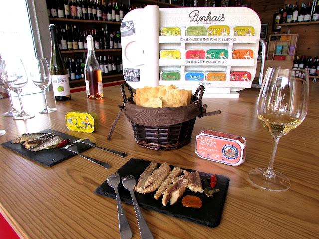 mesa com provas de peixes em conservas e copos com vinho