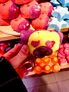 A yellow pug shaped bubble bar with red heart shaped eyes held by a pale white hand on a bright background