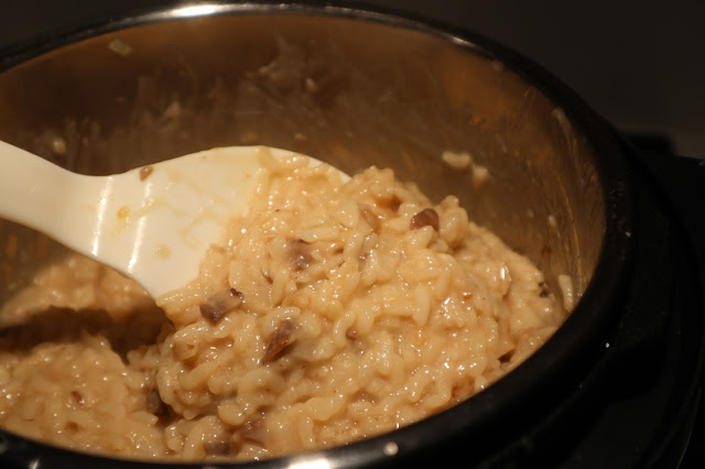 A spoon stirring the creamy mixture of mushroom risotto