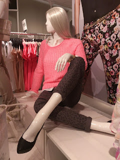 Mannequin in pants surrounded by clothes.jpeg