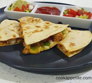Easy chicken quesadillas packed with onion, garlic and herb, pepper, diced tomato, mozzarella cheese, cheddar cheese and chicken. Chicken Quesadillas Served with tomato sauce and salsa.  Golden brown, crispy chicken quesadillas full of chicken, vegetable and cheese flavor.