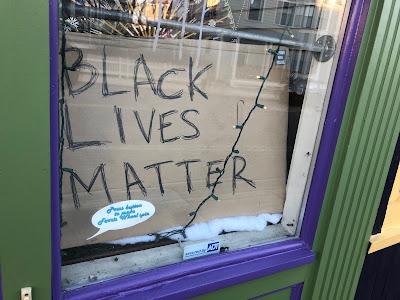 """""""Black Lives Matter"""" in small business window, written on cardboard in pen."""