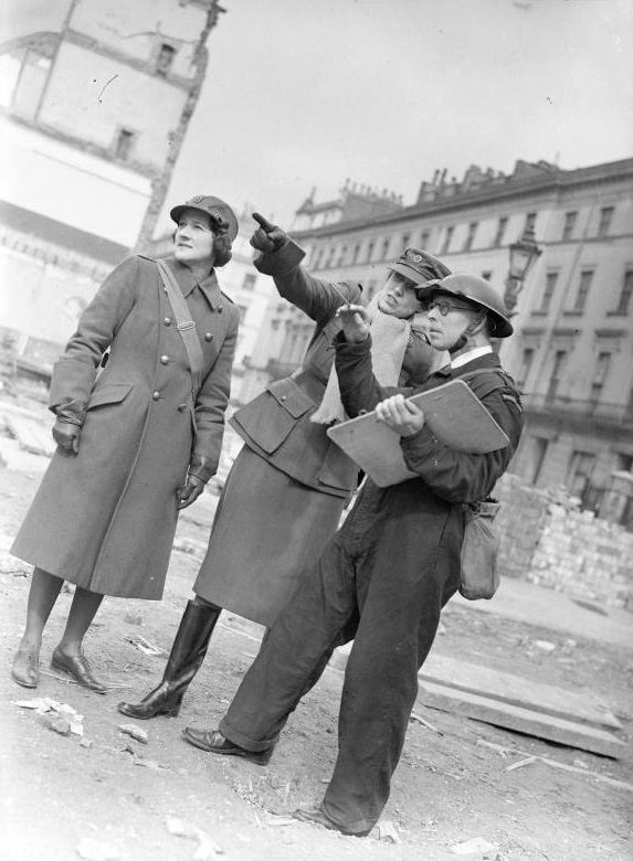 Women of the WW2 MTC - Miss Winifred Ashford points something out to an Air Raid Precautions (ARP) Warden with a clipboard, as Mrs Pat Macleod looks on. The Warden is based at Paddington ARP station. Behind them can be seen an empty space that once held houses before they were destroyed in an air raid.