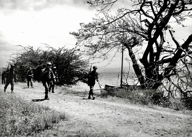 Infantry troops of Company K, 3rd Battalion, 158th Regimental Combat Team, move along the road near Batangas Bay, Luzon, P.I. Taken 12 March 1945.