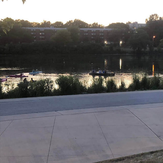 Kayakers rowing up to listen to the show at RiverEdge Park in Aurora, Illinois