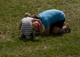 A child and parent looking curiously at something on the ground.