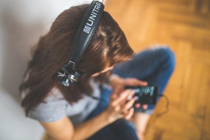 Mulher sentada no chão, usando headphone, usando o celular, ângulo superior que não mostra o rosto dela