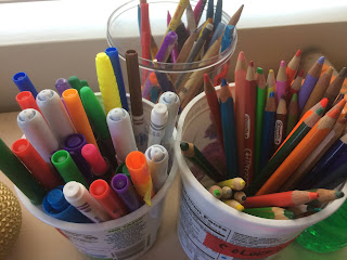 Yogurt containers with pencils and pens