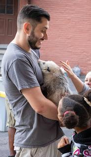 Children pet Daisy the opossum