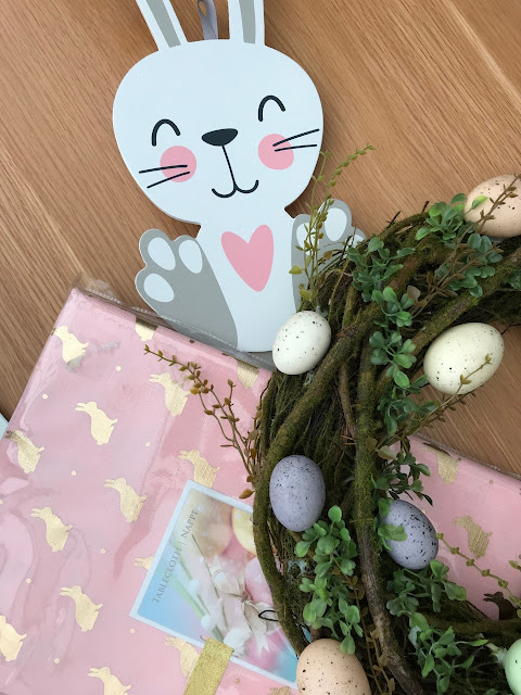 Easter wreath, bunny tablecloth, and a wooden bunny sign